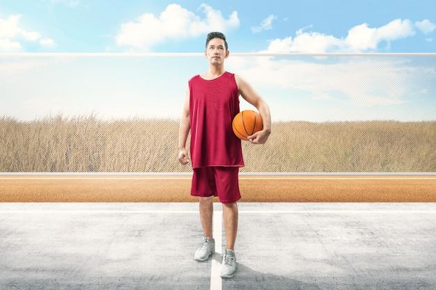 Hübscher asiatischer mann mit der sportuniform, die den ball trägt