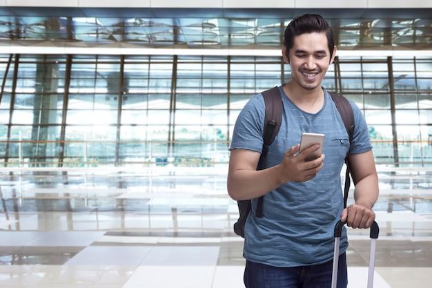 Hübscher asiatischer mannreisender mit dem koffer, der smartphone hält