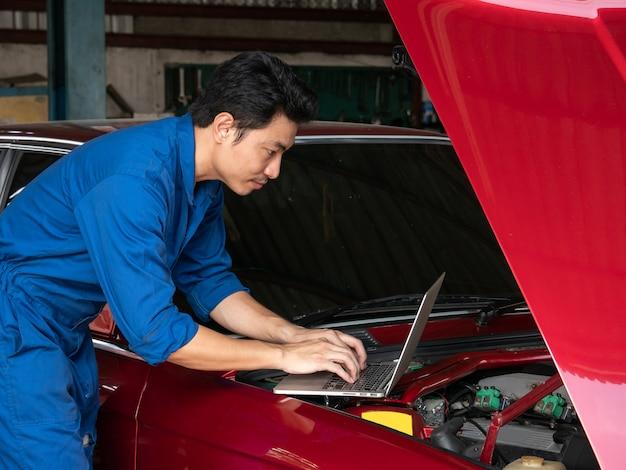 Hübscher asiatischer mechaniker, der laptop-computer verwendet, um einen automotor zu überprüfen und sich daumen an der reparaturgarage zu zeigen.