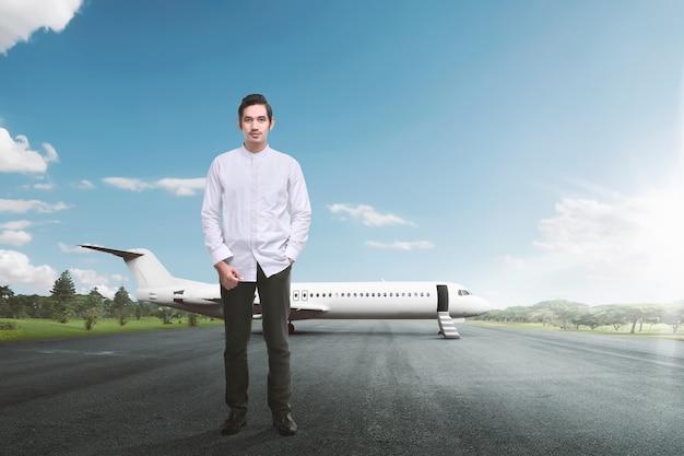 Hübscher asiatischer moslemischer mann, der mit flugzeug steht