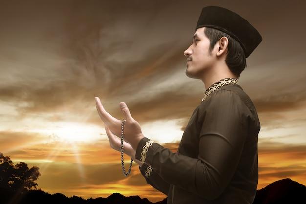 Hübscher asiatischer moslemischer mann mit gebetsperlen