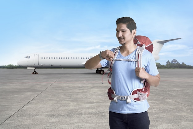 Hübscher asiatischer tourist mit rucksack zeit überprüfend, bevor sie abreisen