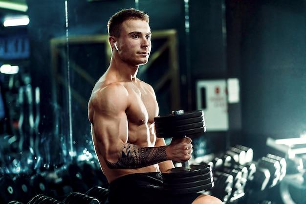 Hübscher athlet des jungen erwachsenen mannes, der in der turnhalle ausarbeitet, auf einer bank sitzt und dummkopf mit den angehobenen armen hält. innen, gewicht schauend