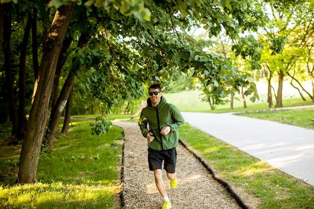 Hübscher athletischer junger mann, der während des trainings im sonnigen grünen park läuft