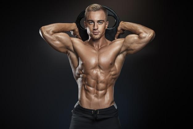 Hübscher athletischer kerl, der mit barbellplatte aufwirft