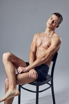 Hübscher athletischer mann, der auf stuhl isolierte wand sitzt.
