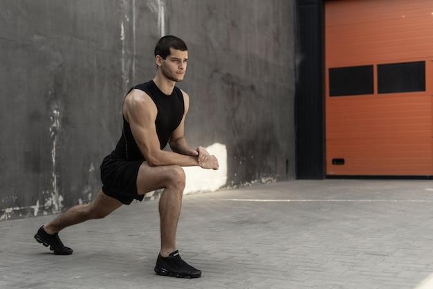 Hübscher, athletischer mann, der sich vor dem training aufwärmend dehnt
