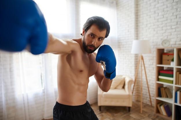 Hübscher athletischer mann in den boxhandschuhen macht durchschlag.