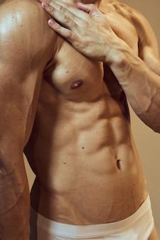 Hübscher athletischer mannkörper mit den aufstellenden muskeln