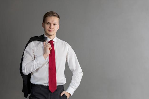 Hübscher, attraktiver blonder mann mit lächeln im anzug, roter krawatte, mantel über der schulter haltend