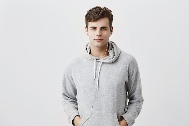 Hübscher attraktiver europäischer mann im grauen kapuzenpulli, mit den händen in den taschen, sieht erfreut aus, hat gute laune, als nach der arbeit nach hause kommt. gut aussehender männlicher student posiert.