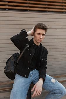 Hübscher attraktiver junger mann in stylischer jeanskleidung glättet trendige frisur