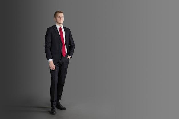 Hübscher, attraktiver mann im anzug und rote krawatte in voller länge auf grauer wand