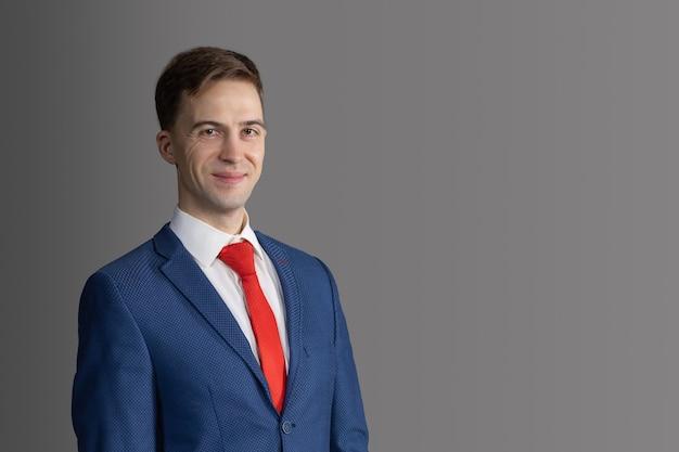 Hübscher, attraktiver mann im blauen anzug und in der roten krawatte. selbstbewusster, seriöser geschäftsmann, anwalt, geschäftsführer lächelt.
