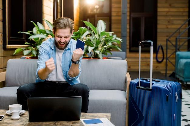 Hübscher aufgeregter junger mann sitzt am sofa in der hotellobby mit laptop und reisepass in den händen