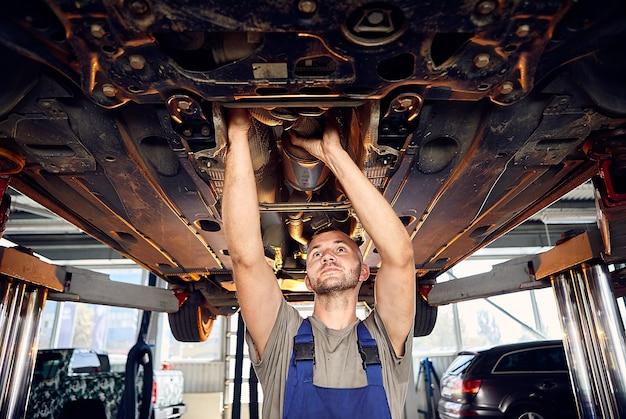 Hübscher automechaniker, der fahrwerk des automobils auf tankstelle prüft.