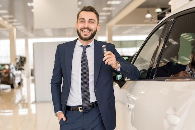 Hübscher autoverkäufer, der schlüssel hält