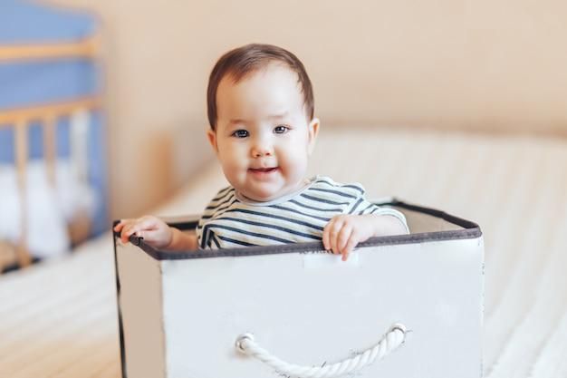 Hübscher babykindjunge oder -mädchen, die innerhalb eines kastens in der wohnung sitzen