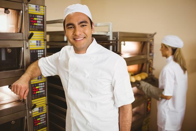 Hübscher bäcker, der an der kamera lächelt