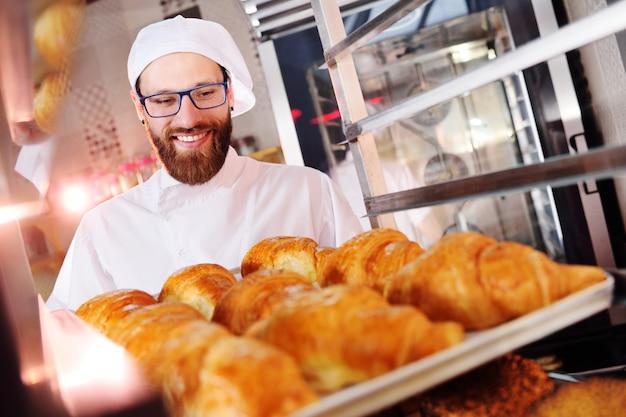 Hübscher bäcker in der weißen uniform, die in seinen händen einen behälter voll von frisch gebackenen hörnchen hält