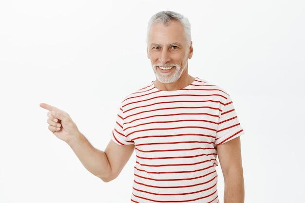 Hübscher bärtiger älterer mann, der finger nach links zeigt und werbung zeigt