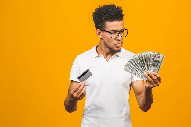 Hübscher bärtiger afroamerikanermann, der stapel geld und eine kreditkarte hält