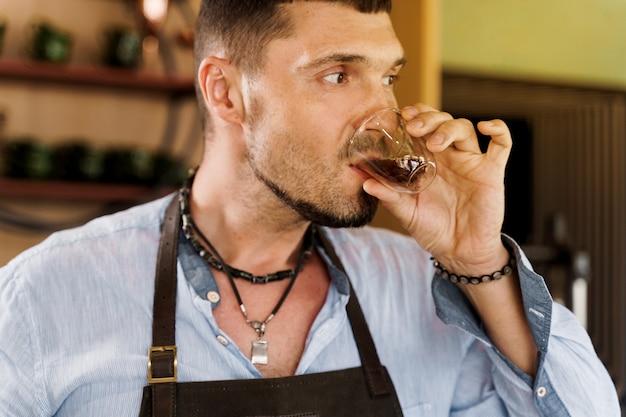 Hübscher bärtiger barista trinkt espressokaffee in der doppelten glasschale
