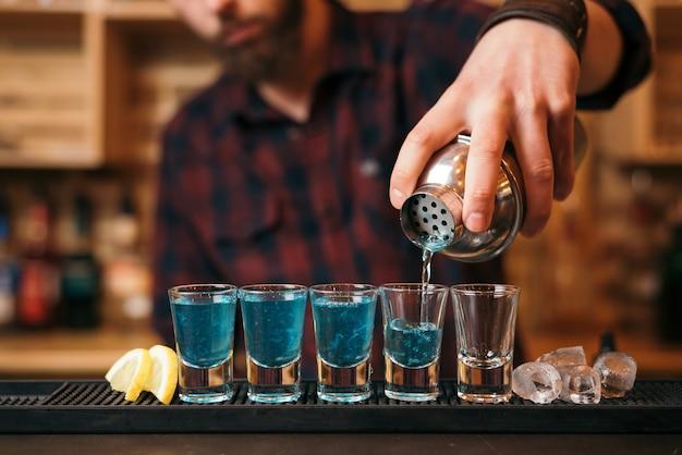 Hübscher bärtiger barmann macht cocktails im nachtclub.