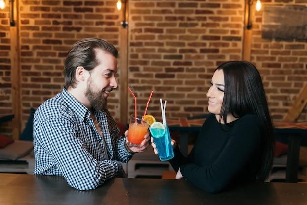 Hübscher bärtiger barmann und schöne junge brünette frau, die im nachtclub mit blauer lagune und tequila-sonnenaufgang-cocktail anstoßen.