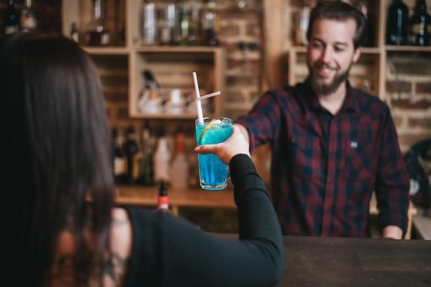Hübscher bärtiger barmann und schöne junge brünette frau, die in der cafébar mit blauem lagunencocktail rösten. selektiver fokus auf glas.