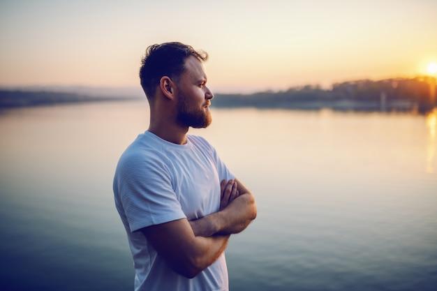 Hübscher bärtiger blonder kaukasischer mann, der auf klippe mit verschränkten armen steht und schönen sonnenuntergang betrachtet.