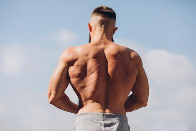 Hübscher bärtiger bodybuilder-mann mit perfektem muskelkörper, der draußen auf dem himmelhintergrund aufwirft. starker mann mit nacktem oberkörper, der wegschaut. blick von hinten