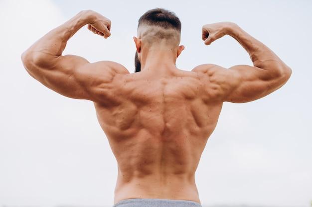 Hübscher bärtiger bodybuilder-mann mit perfektem muskelkörper, der draußen auf dem himmelhintergrund aufwirft. starker mann mit nacktem oberkörper stehend