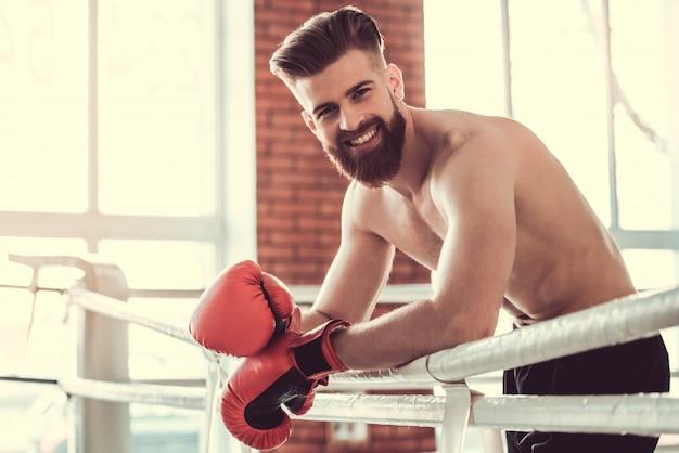 Hübscher bärtiger boxer mit dem bloßen torso in den roten handschuhen.