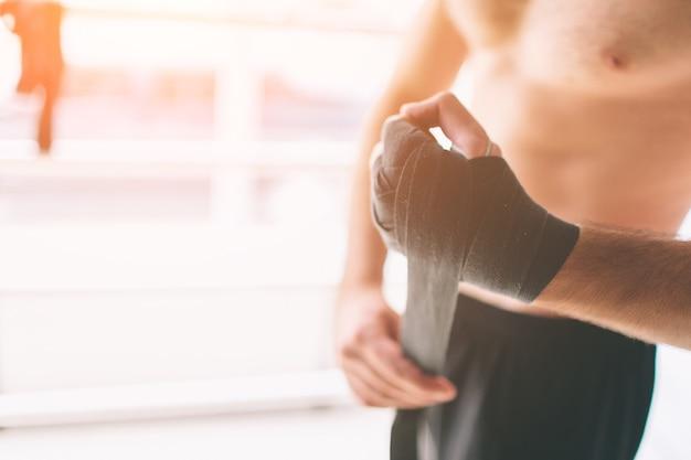 Hübscher bärtiger boxer mit nacktem oberkörper, der seine hände umwickelt und bereit ist, im kampfclub zu kämpfen