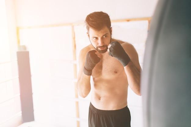 Hübscher bärtiger boxer mit nacktem oberkörper übt schläge im kampfclub