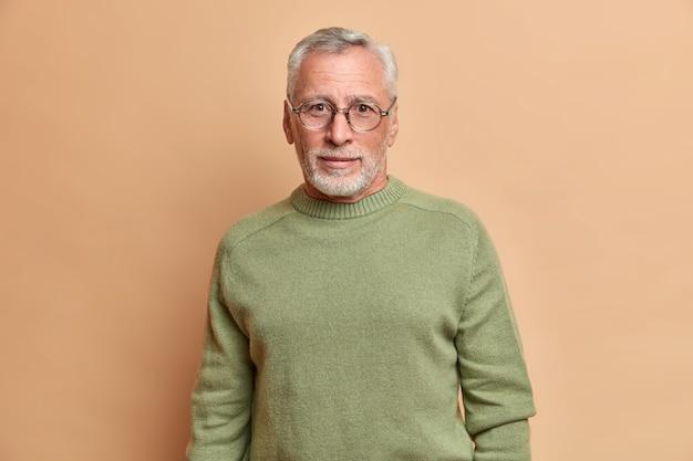Hübscher bärtiger europäischer mann mit neugierigem blick trägt brille und grundpullover schaut direkt auf vordere posen gegen beige wand