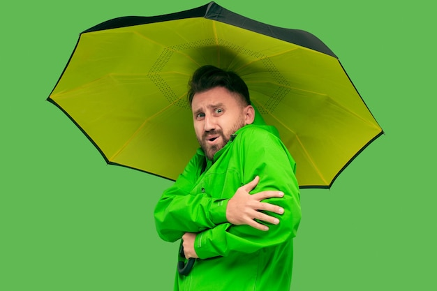 Hübscher bärtiger frierender junger mann, der regenschirm hält und kamera lokalisiert auf lebendigem trendigem grünem studio betrachtet.