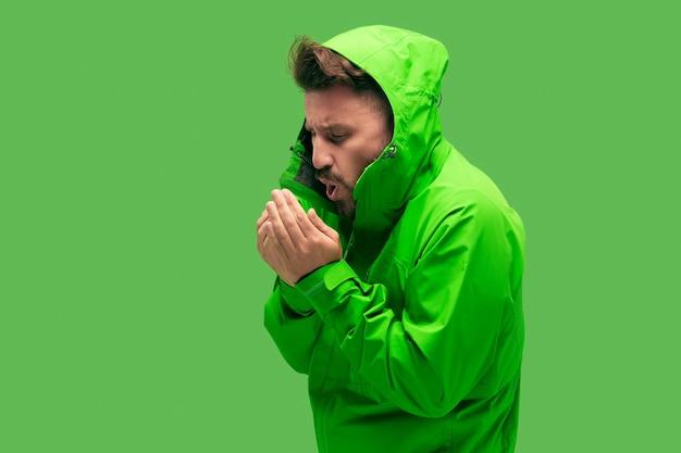 Hübscher bärtiger frierender junger mann lokalisiert auf lebendiger trendiger grüner farbe im studio.