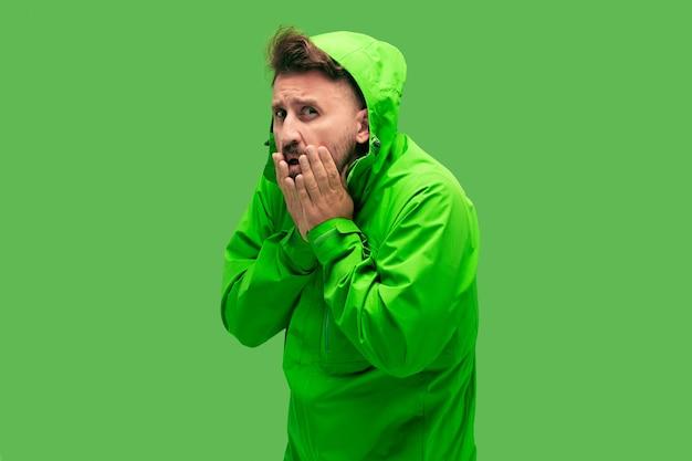 Hübscher bärtiger frierender junger mann lokalisiert auf lebendiger trendiger grüner farbe im studio