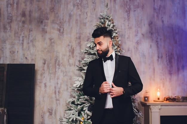 Hübscher bärtiger geschäftsmann im klassischen anzug mit weihnachtsbaum