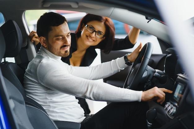 Hübscher bärtiger geschäftsmann sitzt in einem neuen auto im autohaus