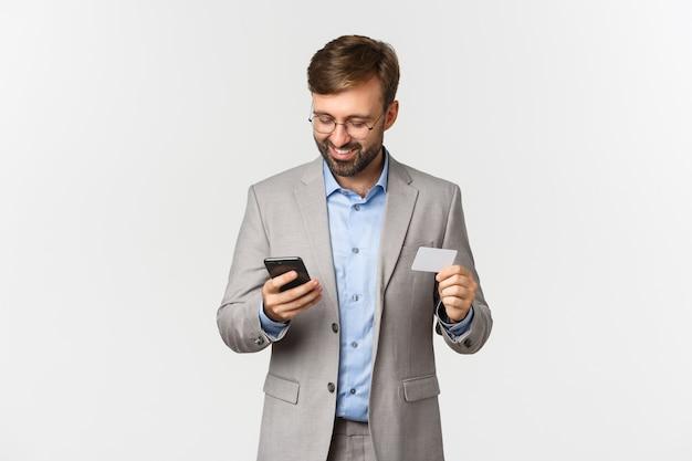 Hübscher bärtiger geschäftsmann und brille, online einkaufen, kreditkarte halten