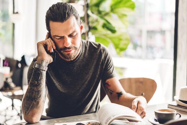 Hübscher bärtiger hippie-manngebrauch smartphone und lesebuch mit kaffee bei tisch im café.
