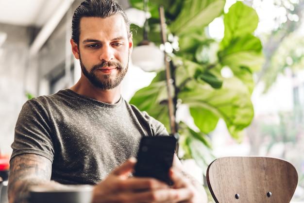 Hübscher bärtiger hipster-mann verwenden smartphone mit kaffee am tisch im café. kommunikations- und technologiekonzept