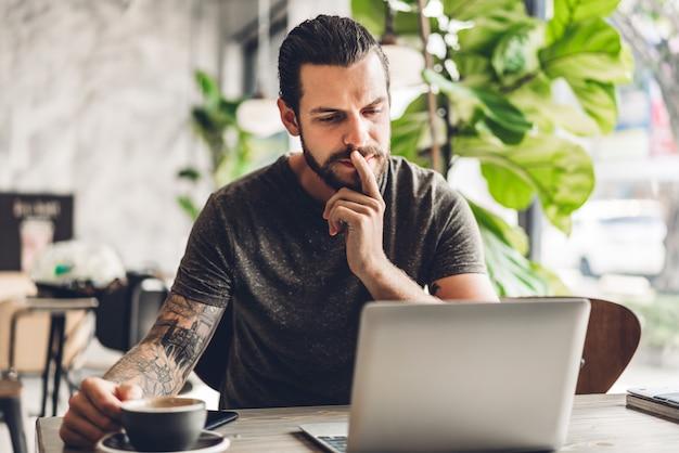 Hübscher bärtiger hipster-mann verwenden und betrachten laptop-computer mit kaffee am tisch im café. kommunikations- und technologiekonzept