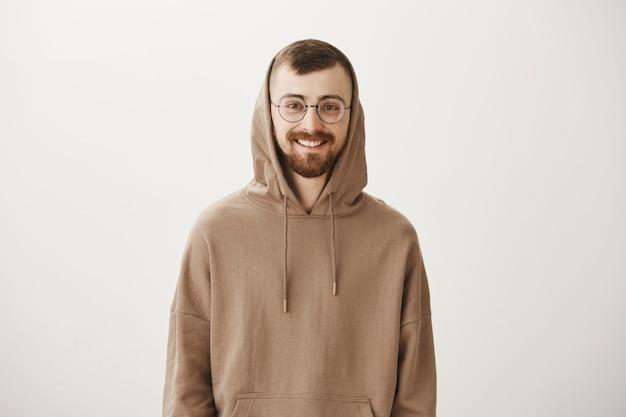 Hübscher bärtiger hipster-typ im kapuzenpulli und in der lächelnden brille