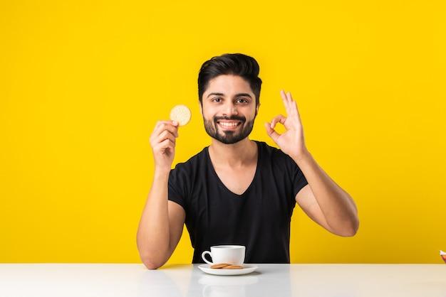 Hübscher bärtiger indischer mann, der gesunde vollkornkekse isst, die in kaffee von tee oder chai in einer tasse getaucht sind und am tisch vor gelbem hintergrund sitzen