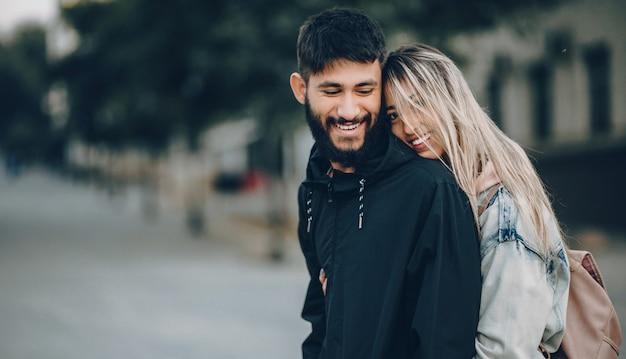 Hübscher bärtiger junge, der von seinem kaukasischen blonden mädchen umarmt wird, während er geht und fröhlich lächelt