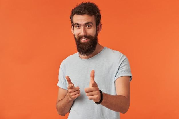 Hübscher bärtiger junger kerl, der mit den fingern nach vorne zeigt